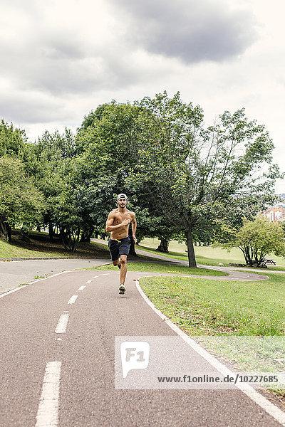 Sportlicher junger Mann beim Joggen im Park