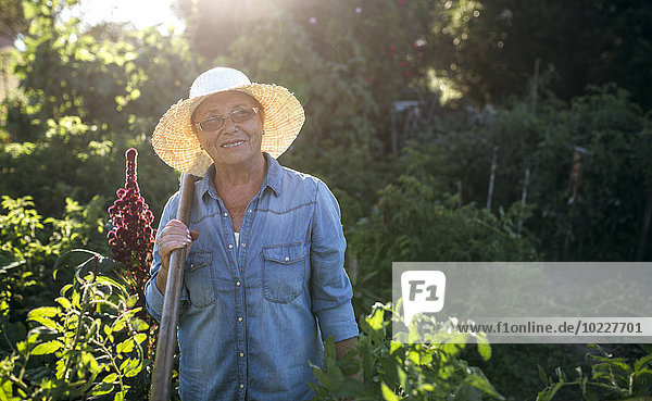 Porträt der lächelnden Seniorin mit Strohhut im Garten