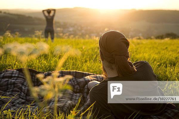 Deutschland  Paar auf einer Wiese beim Sonnenaufgang