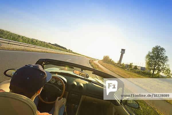 Teenager beim Fahren auf einer Landstraße in einem Cabriolet