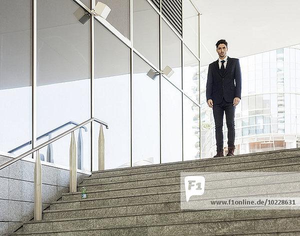 Porträt eines jungen Geschäftsmannes am oberen Ende der Treppe