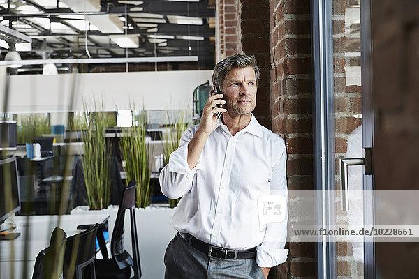 Geschäftsmann im Büro auf dem Smartphone mit Blick aus dem Fenster