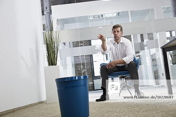 Geschäftsmann im Büro wirft zerknittertes Papier in Papierkorb
