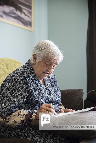 Seniorin beim Kreuzworträtselspiel zu Hause