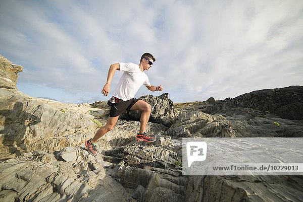 Spanien  Valdovino  junger Mann läuft auf den Felsen