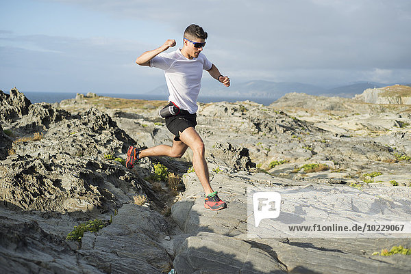 Spanien  Valdovino  junger Mann beim Trailrunning in einer felsigen Landschaft