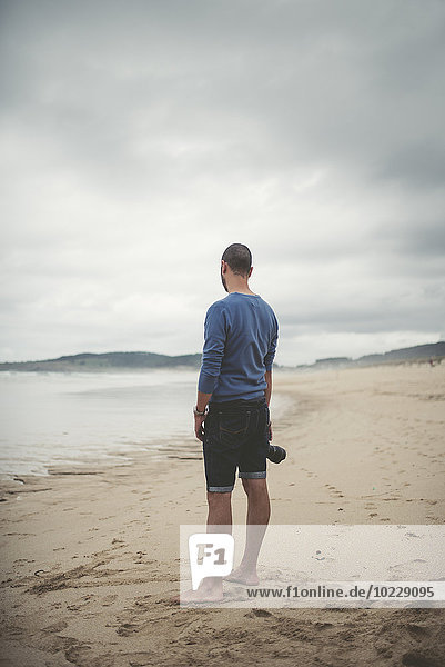 Spain  Ferrol  man with camera standing on the beach