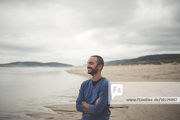Spanien  Ferrol  Porträt eines lächelnden Mannes mit verschränkten Armen am Strand
