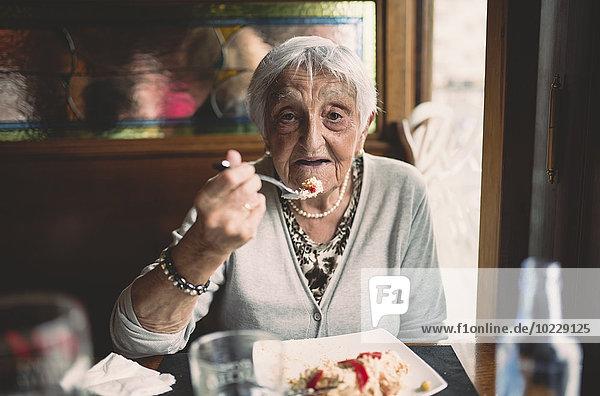 Porträt einer lächelnden Seniorin beim Essen in einem Restaurant