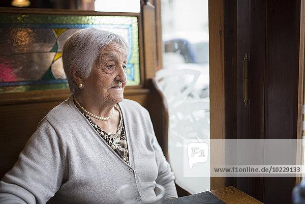Porträt einer älteren Frau  die in einem Restaurant sitzt und durchs Fenster schaut.