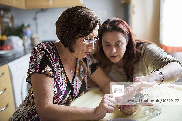 Frau hilft Seniorin  wie man ein Smartphone benutzt
