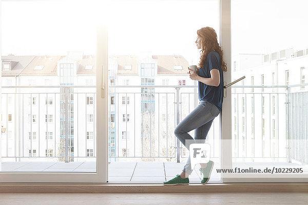 Junge Frau  die sich an der Schiebetür des Balkons lehnt und in die Ferne blickt Junge Frau, die sich an der Schiebetür des Balkons lehnt und in die Ferne blickt