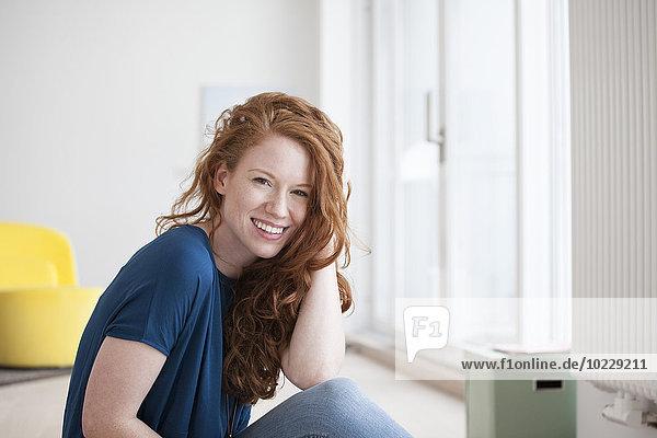 Porträt einer glücklichen jungen Frau  die auf dem Boden ihres Wohnzimmers sitzt.
