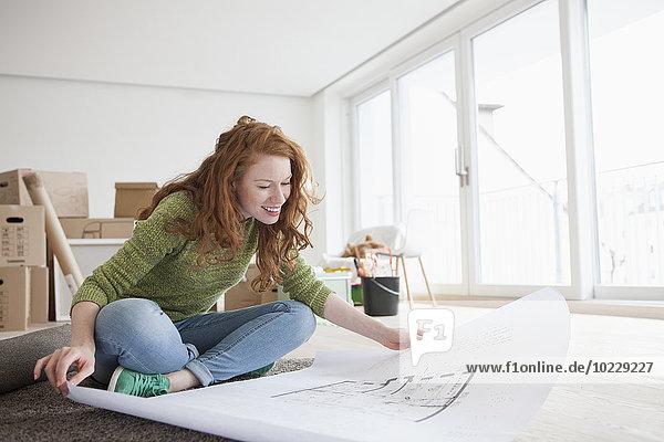 Junge Frau in neuer Wohnung mit Kartons im Grundriss