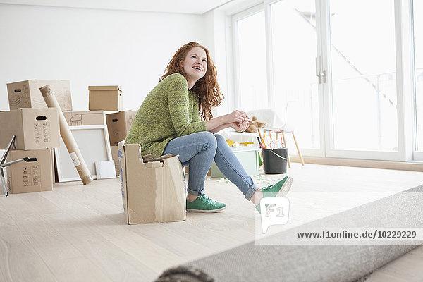 Young woman in new flat sitting on cardboard box