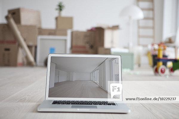 Laptop mit Bild des leeren Raumes vor gestapelten Kartons Laptop mit Bild des leeren Raumes vor gestapelten Kartons