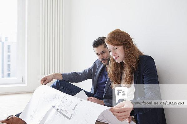 Junges Paar sitzt auf dem Boden seiner neuen Wohnung und schaut sich den Grundriss an.