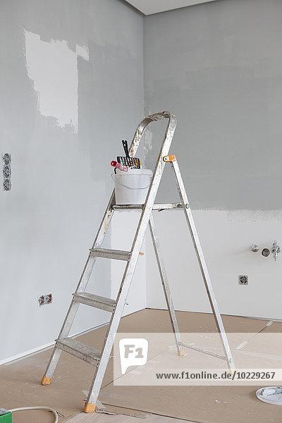 Farbeimer und Rolle auf Leiter Farbeimer und Rolle auf Leiter