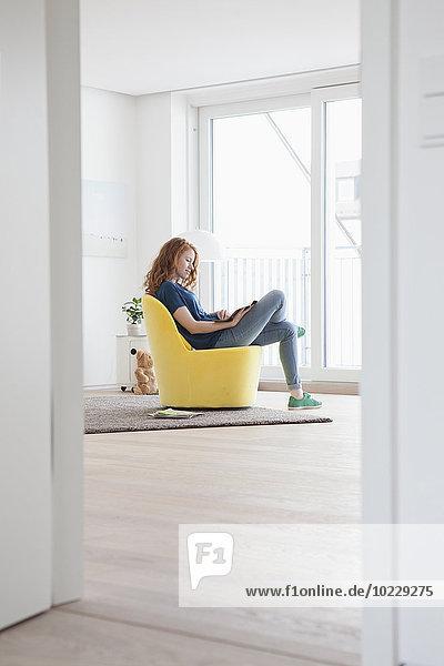 Junge Frau auf gelbem Sessel im Wohnzimmer sitzend