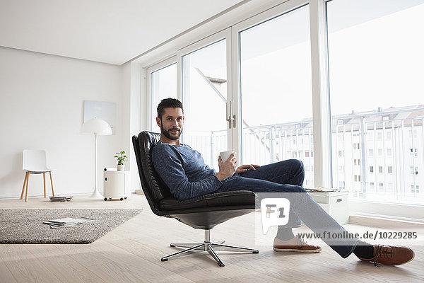 Junger Mann entspannt auf Lederstuhl mit Tasse Kaffee