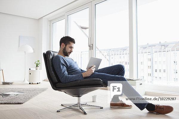 Junger Mann sitzt auf einem Ledersessel in seinem Wohnzimmer und benutzt ein digitales Tablett.
