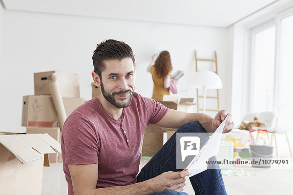 Junges Paar zieht in neue Wohnung  Mann mit Grundriss