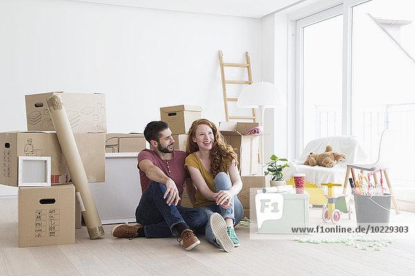 Junges Paar in neuer Wohnung mit Kartons  auf dem Boden sitzend