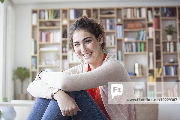 Porträt der lächelnden jungen Frau zu Hause