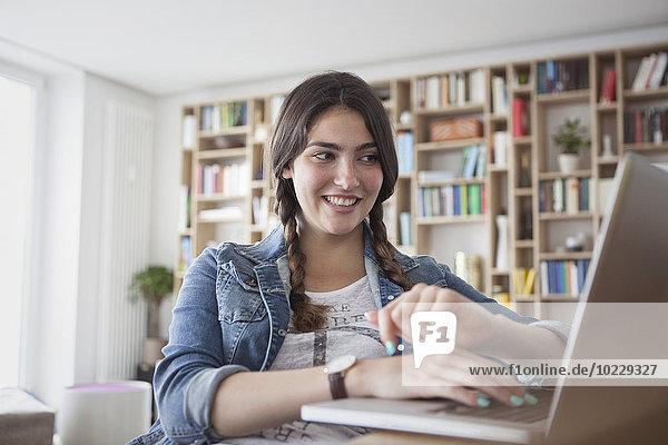 Porträt einer lächelnden jungen Frau mit Laptop zu Hause