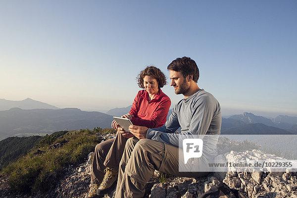 Österreich  Tirol  Unterberghorn  zwei Wanderer sitzend mit digitalem Tablett in alpiner Landschaft