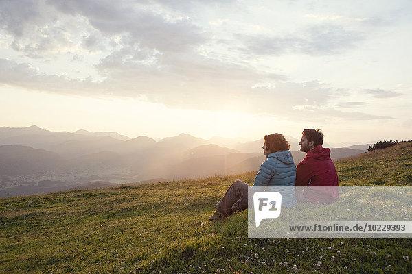 Austria  Tyrol  Unterberghorn  two hikers resting in alpine landscape at sunrise