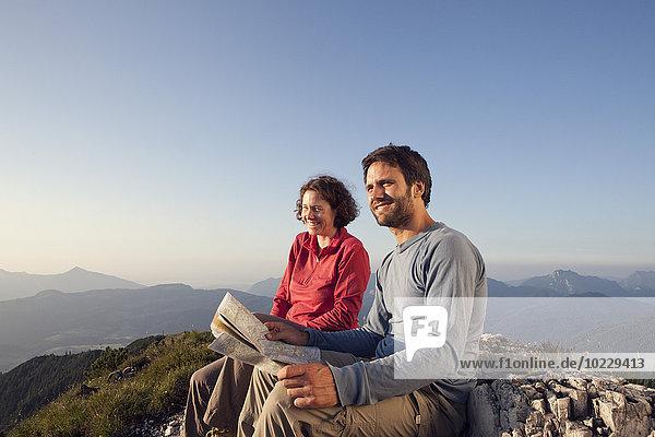 Österreich  Tirol  Unterberghorn  zwei Wanderer sitzend mit Karte in alpiner Landschaft