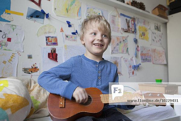 Porträt eines lächelnden kleinen Jungen  der auf dem Bett seines Zimmers sitzt und Gitarre spielt. Porträt eines lächelnden kleinen Jungen, der auf dem Bett seines Zimmers sitzt und Gitarre spielt.