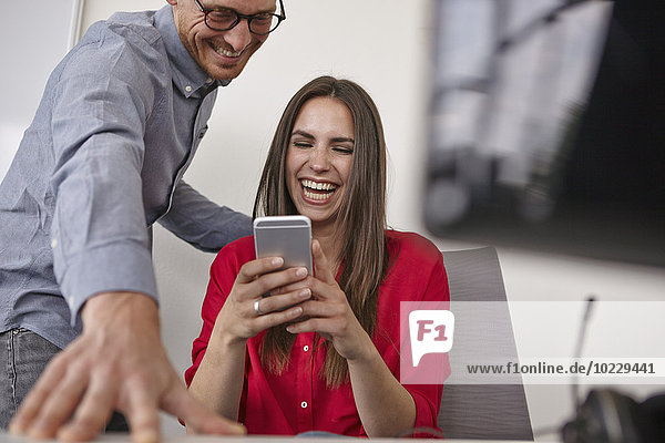 Happy man and woman in office looking on cell phone