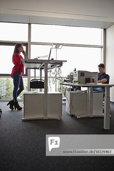 Junge Frau im Büro telefoniert am verstellbaren Schreibtisch
