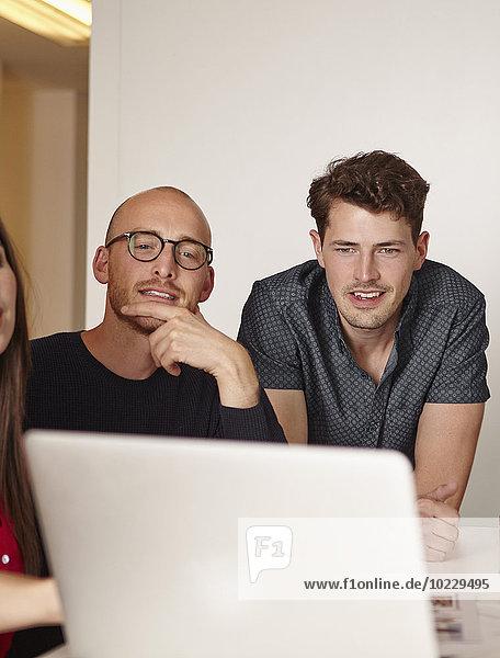 Zwei Männer im Büro beim Blick auf den Laptop