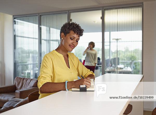Junge Frau im Büro schreibt in Notizbuch