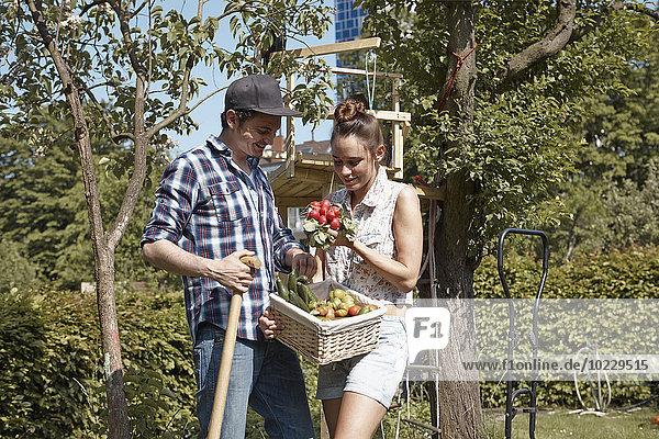 Lächelndes Paar im Garten mit frischem Gemüse