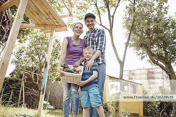 Stolze Familie präsentiert Korb mit frischem Gemüse im Garten