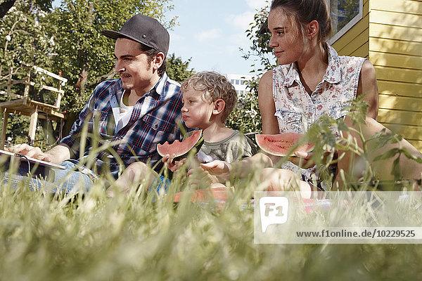 Familie im Garten essen Wassermelonenscheiben