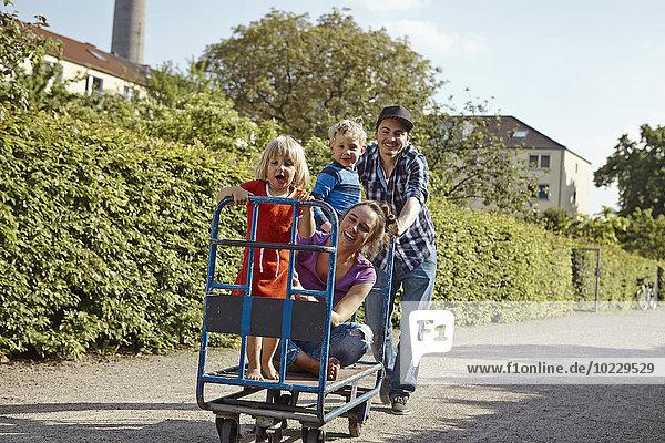 Vater Schiebewagen mit Familie im Kleingartenbereich