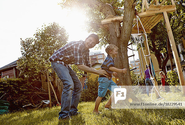 Glückliche Familie beim Spielen im Garten