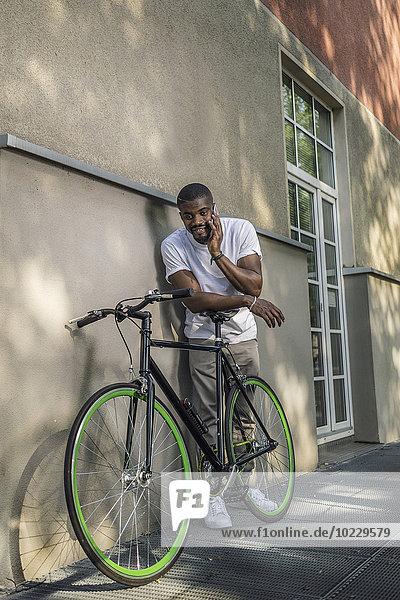 Portrait eines jungen Mannes mit Fahrradtelefonie mit Smartphone