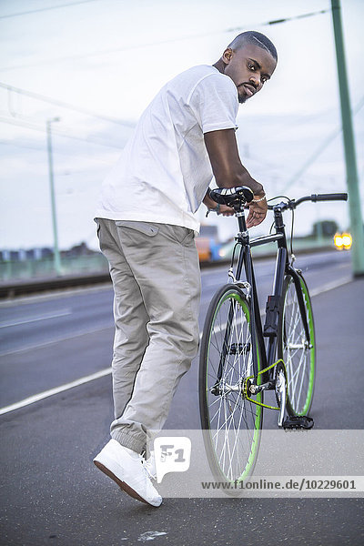 Portrait eines jungen Mannes mit Fahrrad