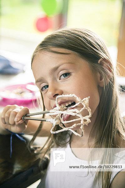 Porträt eines kleinen Mädchens  das Schlagsahne vom Rührer leckt.