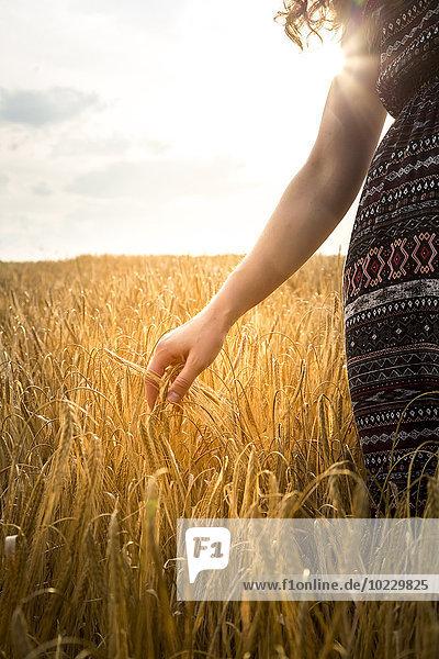 Junge Frau am Abend im Gerstenfeld stehend