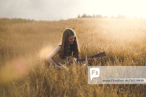 Young woman playing guitar in field in the evening