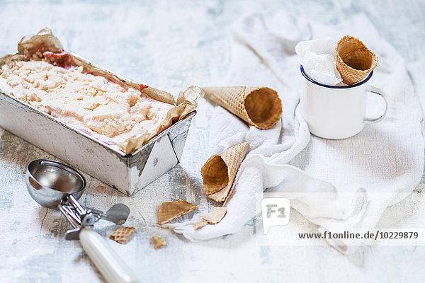 Vanilleeis in der Brotpfanne  Emaillebecher mit Eistüte und Eiskugelzange