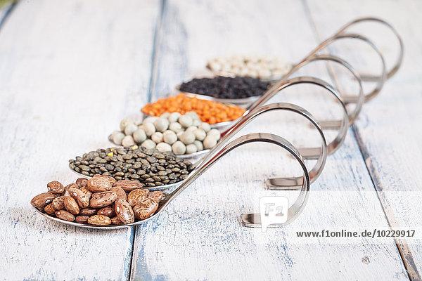 Löffelreihe mit verschiedenen getrockneten Hülsenfrüchten