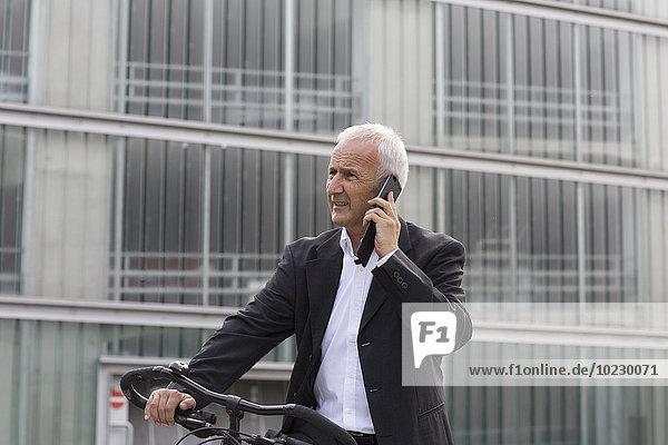 Geschäftsmann mit Fahrradtelefonie mit Smartphone